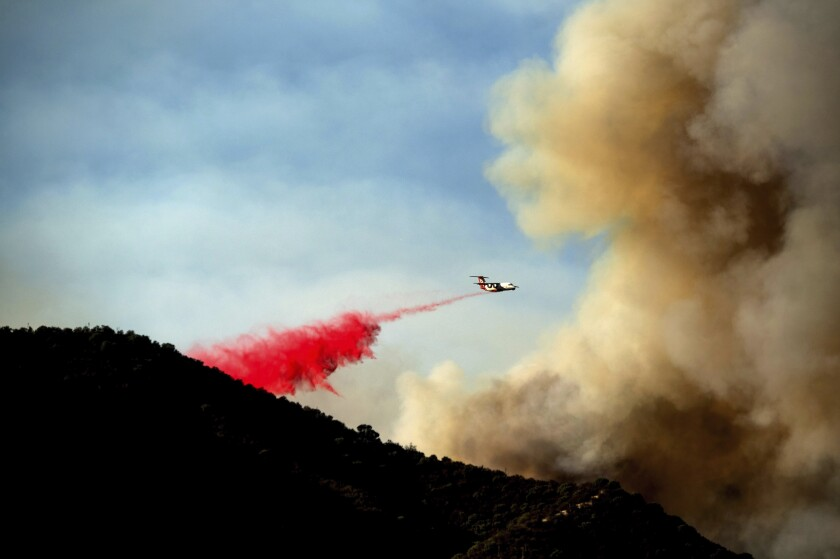 An air tanker drops retardant as the Lake Fire burns in the Angeles National Forest north of Santa Clarita, Calif., on Thursday, Aug. 13, 2020. (AP Photo/Noah Berger)