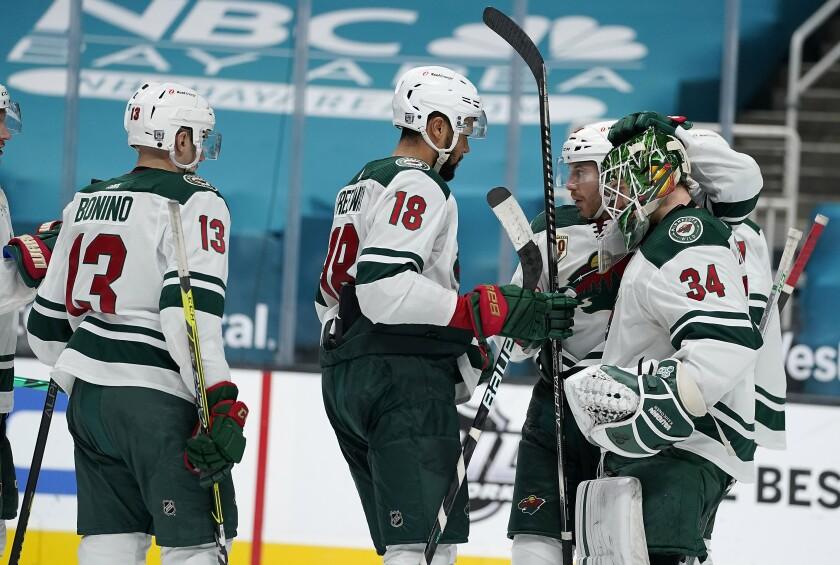 Minnesota Wild goaltender Kaapo Kahkonen (34) is congratulated by teammates after their victory over the San Jose Sharks in an NHL hockey game in San Jose, Calif., Monday, Feb. 22, 2021. (AP Photo/Tony Avelar)