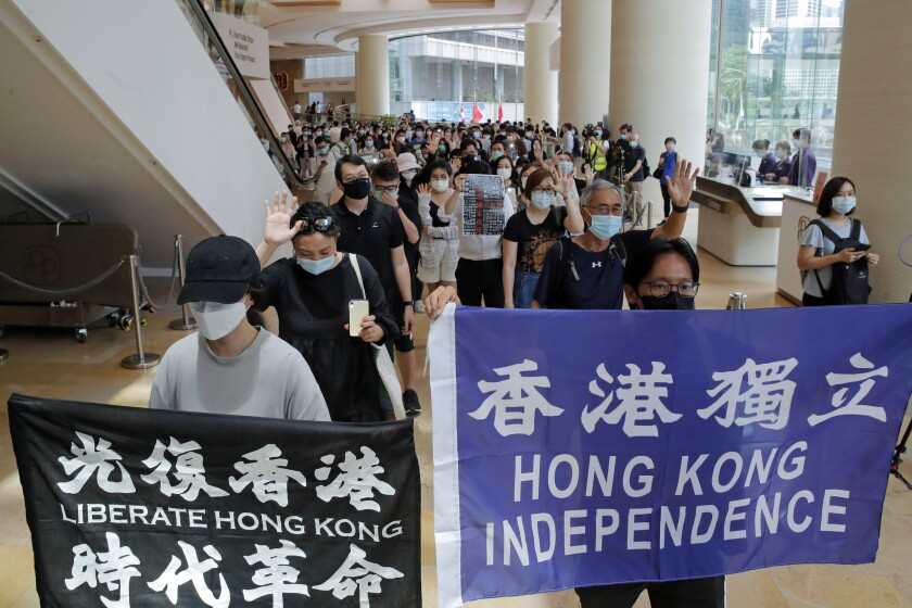 Protesters hold flags in a shopping mall during a protest in Hong Kong, Friday, June 12, 2020. Protesters in Hong Kong got its government to withdraw extradition legislation last year, but now they're getting a more dreaded national security law. And the message from Beijing is that protest is futile. (AP Photo/Kin Cheung)