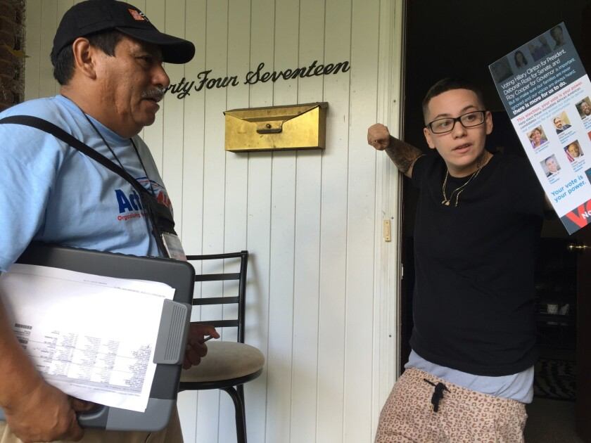 Rogelio Reyes, left, talks with Krista Talbot, 25, who said she is motivated to vote after the police shooting and anti-transgender bathroom law.