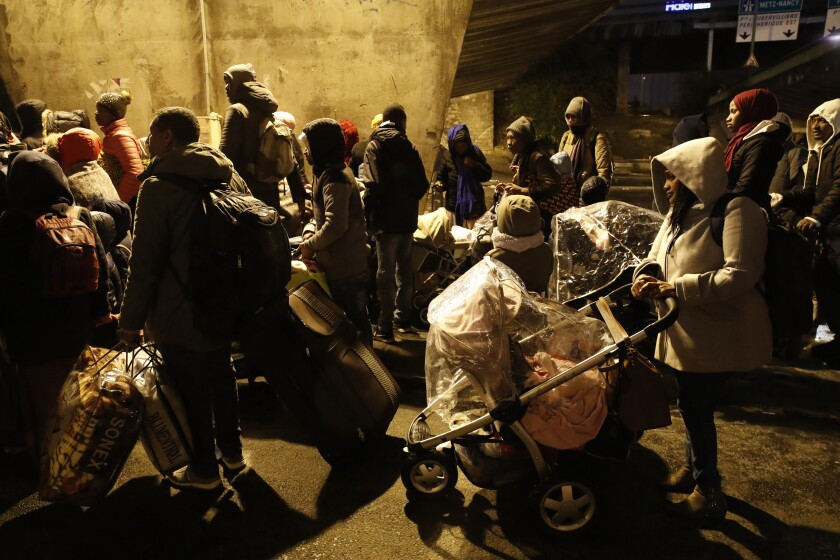 Migrants walk away as police forces clear an area Thursday, Nov. 7, 2019 in the north of Paris. Migrant encampments are becoming increasingly visible in the French capital. Police cleares Thursday several thousand people from a northern Paris neighborhood where migrants have repeatedly been removed. They are taken to shelters, and some eventually sent home. (AP Photo/Francois Mori)