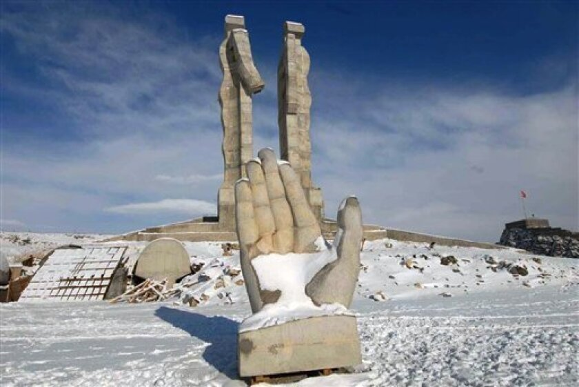 "FILE - Undated but recent file photo shows the monument that features a divided human figure, with one half extending a hand to the other half, symbolizing the pain of division and the hope of reconciliation, sculpted from stone by Mehmet Aksoy, a prominent Turkish artist, in the eastern city of Kars, Turkey. Modern art or a blight on the landscape? A giant monument to friendship between historic enemies Turkey and Armenia has become a symbol of controversy rather than healing. Turkey's prime minister said the monument near the Armenian border is a ""freak"" that overshadows a nearby Islamic shrine, underscoring complex tensions in predominantly Muslim Turkey over religious piety and free expression in a society torn between the modern and the traditional.(AP Photo/Mehmet Aksoy, File)"