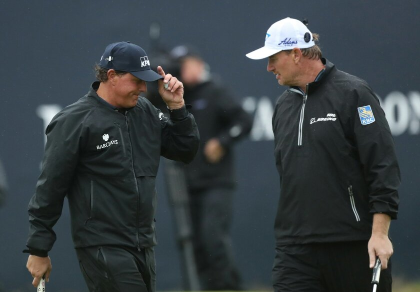 Phil Mickelson of the United States, left,  smiles with Ernie Els of South Africa on the 18th green after he completes his second round of the British Open Golf Championship at the Royal Troon Golf Club in Troon, Scotland, Friday, July 15, 2016. (AP Photo/Peter Morrison)