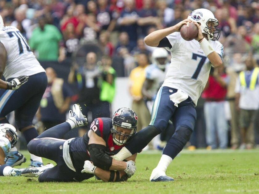 Houston Texans defensive end J.J. Watt (99) sacks Tennessee Titans quarterback Zach Mettenberger during an NFL football game Sunday, Nov. 30, 2014, in Houston. (AP Photo/Conroe Courier, Jason Fochtman)