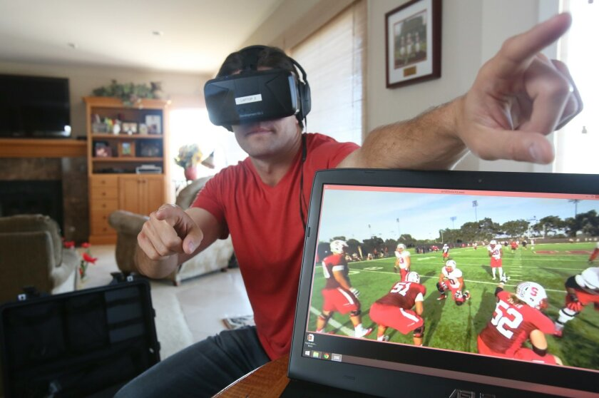 Derek Belch simulates how he can direct players on the field during a demonstration of a virtual reality quarterback training device. Wearing a headset he is able to see what is on the computer screen and turn his head for a different views of the field. photo by Bill Wechter