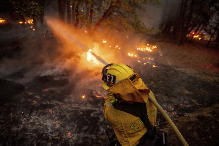 A firefighter battles the Dixie fire in Genesee, Calif., on Saturday.