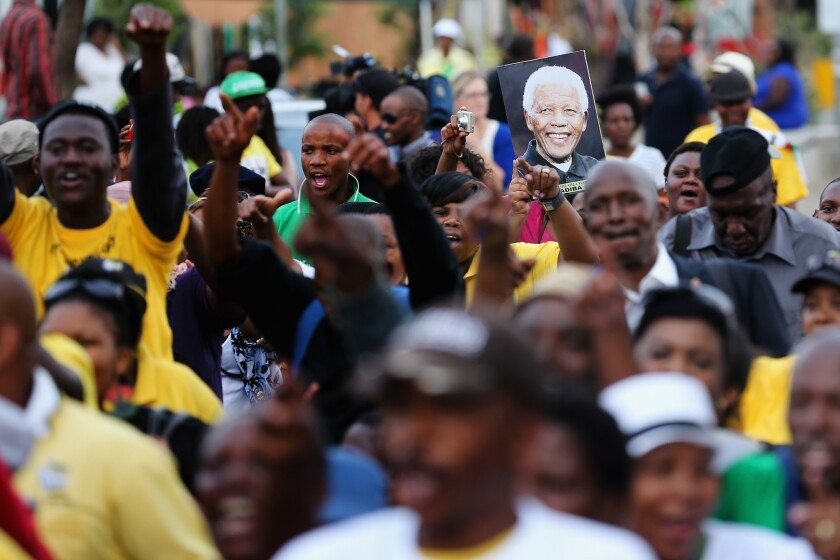 South Africans sing and dance to celebrate the life of Nelson Mandela outside his former home in Soweto on Saturday.
