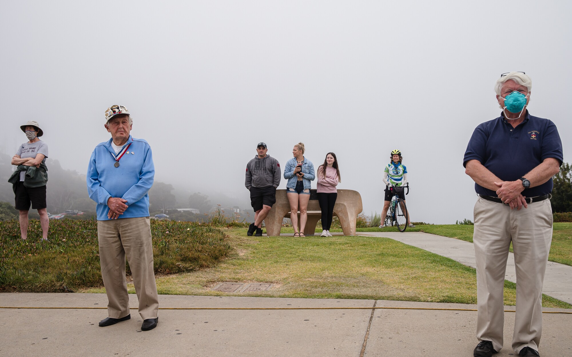Spectators watch at a distance the Memorial Day service at Mt. Soledad National Veterans Memorial on May 25, 2020 in San Diego, California. Due to COVID-19 the Memorial Day remembrance was shown online and not open to the public.