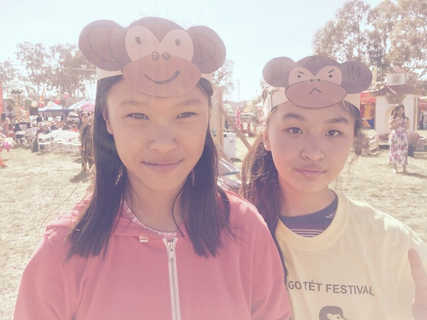 Two girls at the San Diego Tet Festival 2016 in Mira Mesa wear hats to welcome the Year of the Monkey.