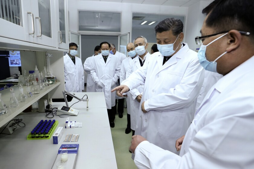 Chinese President Xi Jinping, second right, wearing a protective face mask, talks to a medical staff members during his visit to the Academy of Military Medical Sciences in Beijing. The number of new virus infections rose worldwide along with fears of a weakening global economy,