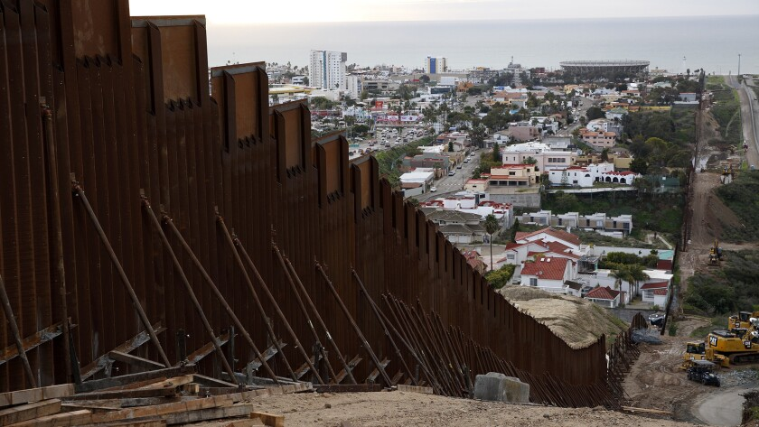 A section of newly-replaced border wall separates Tijuana, Mexico, above left, from San Diego, right, in San Diego. Border Patrol officials say some Mexican homes and structures encroach on U.S. soil posing a dilemma for authorities when replacing the wall.