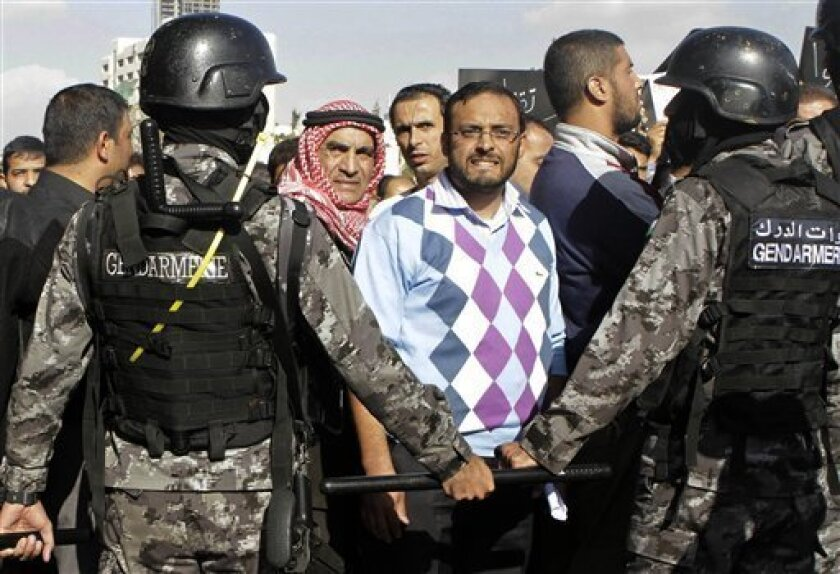 Jordanian police stand guard during a protest against the government's decision to raise prices for subsidized fuel in Amman, Jordan, Monday, Nov. 19, 2012. Nearly a week after the announcement, which sparked unrest that left one person dead and scores wounded, protests across the country continued