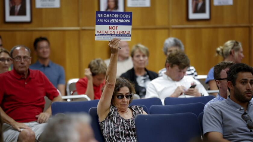Dawn Sassi from University Heights waves her sign showing her opposition to vacation rentals during a San Diego City Council hearing to consider tough new regulations.