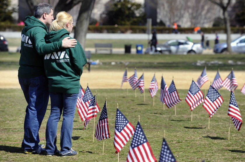 Retired Army Capt. David Dickerson, left, of Oklahoma City, Ok., comforts Abby Malchow, of San Diego, Ca., a Logistic Support sailor among some of the U.S. flags planted to commemorate veterans who have committed suicide. Two of Malchow's close friends committed suicide.