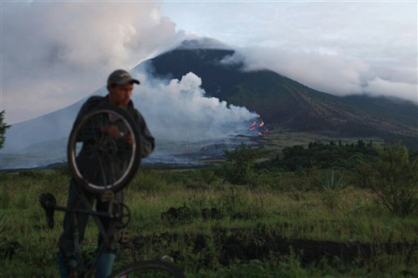 A villager fixes his bicycle next to the erupting Pacaya volcano in Villa Canales, 50 kms south of Guatemala City, Saturday, June 5, 2010. The volcano started erupting lava and rocks last May 27, forcing thousands of people to flee their homes and disrupting air traffic as ash drifted over major ci