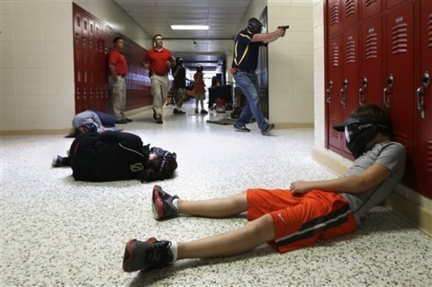 FILE - In this file photo taken July 11, 2013, a Clarksville Schools faculty member, top right, carries an air-powered practice handgun to a classroom as firearms instructors, left, watch and students, lying on the floor, portray victims during a training exercise in Clarksville, Ark. Arkansas' attorney general on Thursday, Aug. 1 said in an opinion issued by his office that the Arkansas board of Private Investigators and Private Security Agencies doesn't have the authority to license school dis