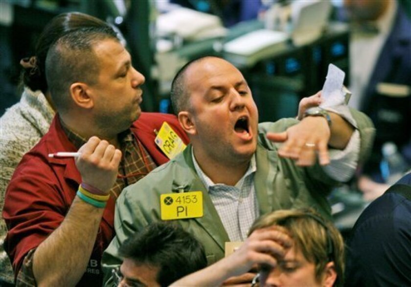 Traders gesture on the floor of the New York Mercantile Exchange in New York, Monday, Jan. 12, 2009. Oil prices fell Monday on concerns over global economic growth, with key U.S. corporate earnings results expected to give a new reading on crude demand in the world's largest consuming nation.   (AP