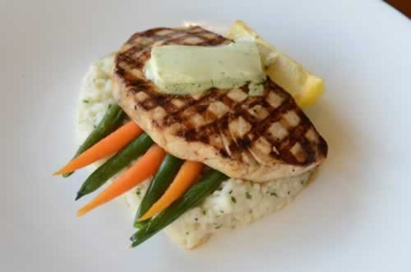 The Signature Grilled Marinated Swordfish with a pat of avocado lime butter is recommended with risotto and cooked vegetables. Photos Kelley Carlson