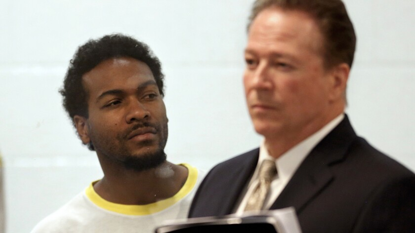 Trenton Trevon Lovell, 27, left, the suspect in the shooting death of L.A. County sheriff's deputy Steve Owen, with public defender John Henderson, during his arraignment in Lancaster.