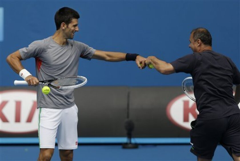 Serbia's Novak Djokovic, left, jokes with a member of his training staff during a training session at the Australian Open tennis championship in Melbourne, Australia, Sunday, Jan. 13, 2013. (AP Photo/Dita Alangkara)