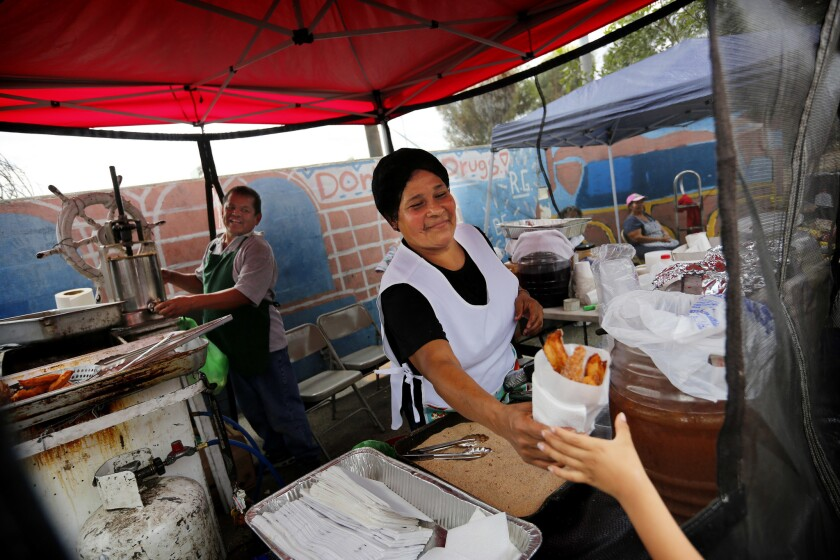 Vendors make churros to be sold for one dollar on Saturday at Ramona Gardens.