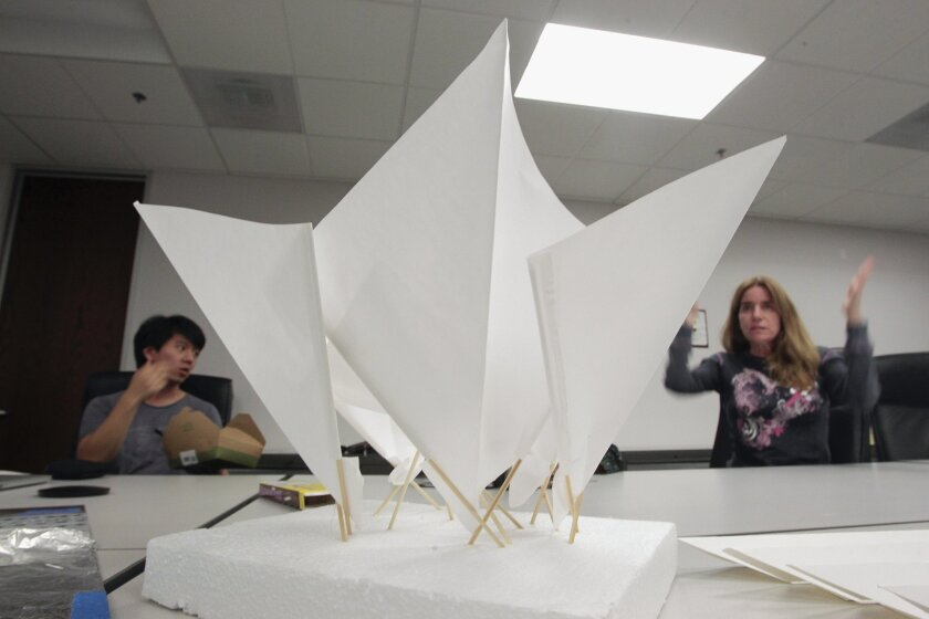 With a model of a sculpture that catches dew sitting on a conference room table in front of them, artist Elizabeth Tobias gestures as she, Materials Science Engineer Dr. Justin Liu, and other members of the Dewers meet at the San Diego Transportation and Storm Water Department in San Diego on Wednesday.