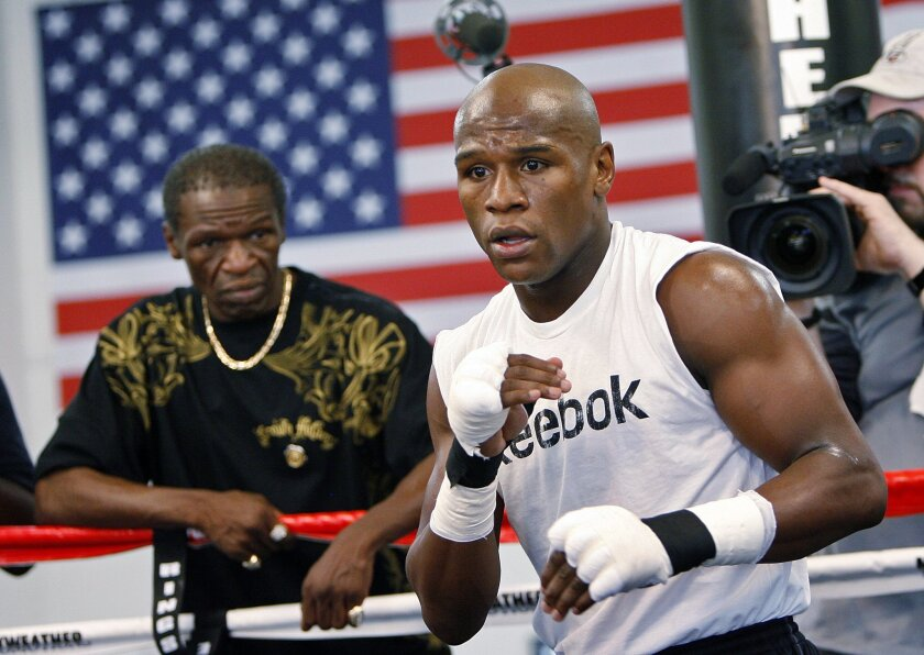 FILE - In this Sept. 19, 2009, file photo, boxier Floyd Mayweather Jr., right, works out at his gym as his father, Floyd Mayweather Sr., left, looks on in Las Vegas. He taught his son to throw punches before he could walk, and he'll be in his corner for the biggest fight of his life against Manny Pacquiao on May 2. The relationship betwee Mayweather Sr. and his son, though, hasn't always been good. (AP Photo/Isaac Brekken, File0