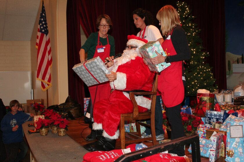 Tresha Souza (standing center), founder of So Others May Eat, Inc.,directs as Santa and volunteers distribute gifts during the agency's annual holiday dinner for the homeless and others in need at Mary, Star of the Sea Catholic Church in La Jolla.