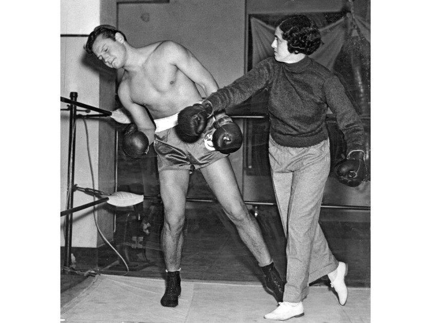 1937 photo of Jack Wofford taking a punch from trainer Belle Martell.