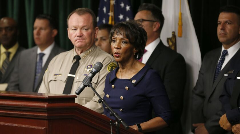 L.A. County Sheriff Jim McDonnell, front left, and L.A. County Dist. Atty. Jackie Lacey have refused to disclose records that are public under California law, according to a lawsuit filed this week by the Los Angeles Times.