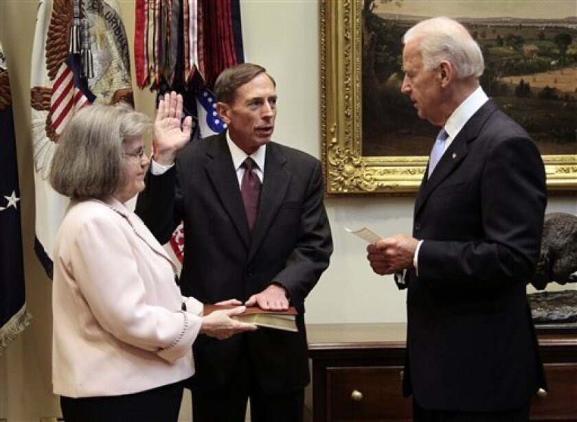 Vice President Joe Biden, right, administers the oath of office to Dir. of the CIA David Petraeus, center, during a swearing-in ceremony in the Roosevelt Room of the White House in Washington, Tuesday, Sept., 6, 2011. Holding a Bible is Petraeus' wife Holly Knowlton Petraeus, left. (AP Photo/Pablo Martinez Monsivais)