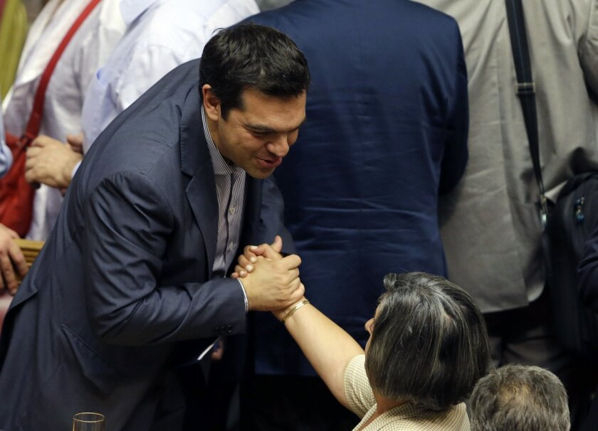 Greece's Prime Minister Alexis Tsipras is greeted by a lawmaker of his Syriza party after a parliament meeting in Athens, Saturday, July 11, 2015. Greek lawmakers have approved a government motion seeking authorization for reform proposals as a basis for negotiations for a third bailout in talks wi