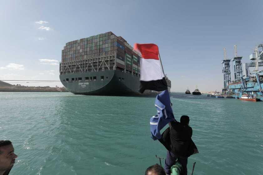 Man waves Egyptian flag alongside Suez Canal