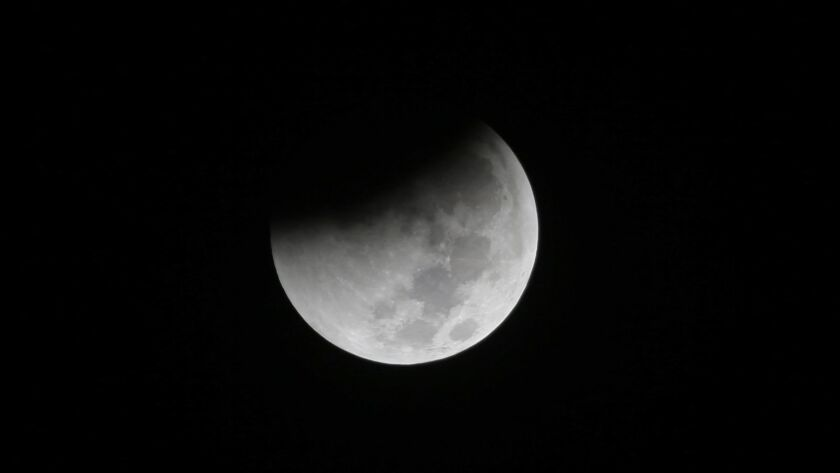 FILE - In this Saturday Aug. 28, 2018 file photo, Earth starts to cast its shadow on the moon during