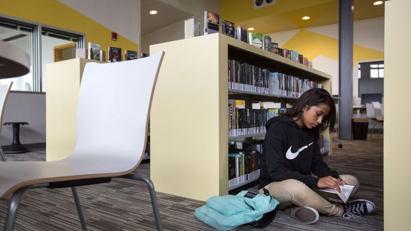 MAYWOOD, CALIF. -- TUESDAY, AUGUST 15, 2017: Student Angela Diaz, pages through a book in the campu