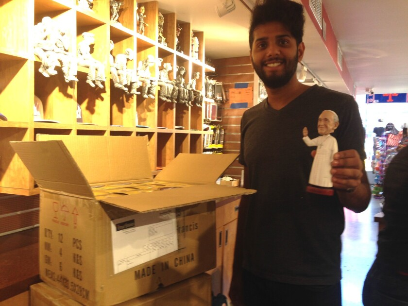 Samir Sabir, at City Souvenirs in Manhattan, opens a fresh supply of bobblehead Pope Francis dolls, which are scarce in New York City.
