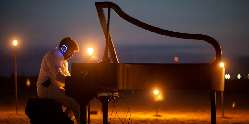 Listen through wireless headphones as composer Murray Hidary, above, plays the piano on the beach at MindTravel's immersive music experience.