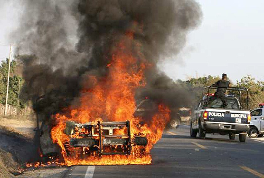 Police officers drive past a burning police vehicle in Zihuatanejo, Mexico. In a three-week period, five grenade attacks were launched on police patrols and stations.