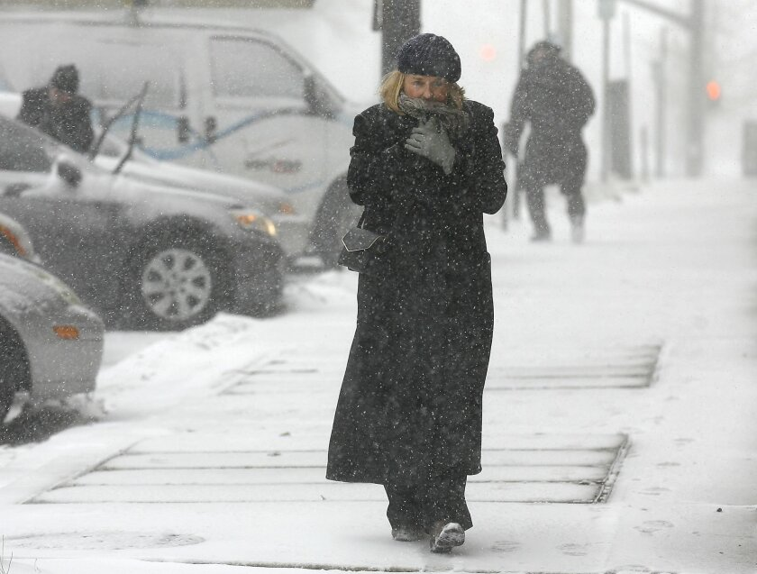 Jean Brown bundles up as she walks in downtown Providence, R.I., during a snow storm, Monday, Feb. 8, 2016.  Massachusetts, Rhode Island and eastern Connecticut, could see winter storm conditions with an accumulation of 4 to 8 inches. The heaviest snowfall is expected during Monday's morning commut