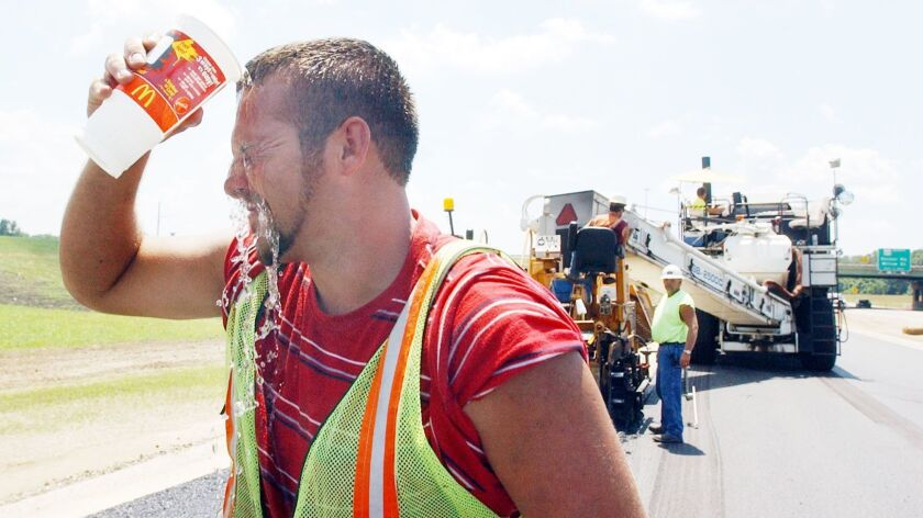 Adam Wilson of Griffin, Ind., cools off as road crews pave U.S. 41 during a 2006 heat wave. Across the country, lost labor productivity due to hotter temperatures could cost $155 billion per year by the end of the century.