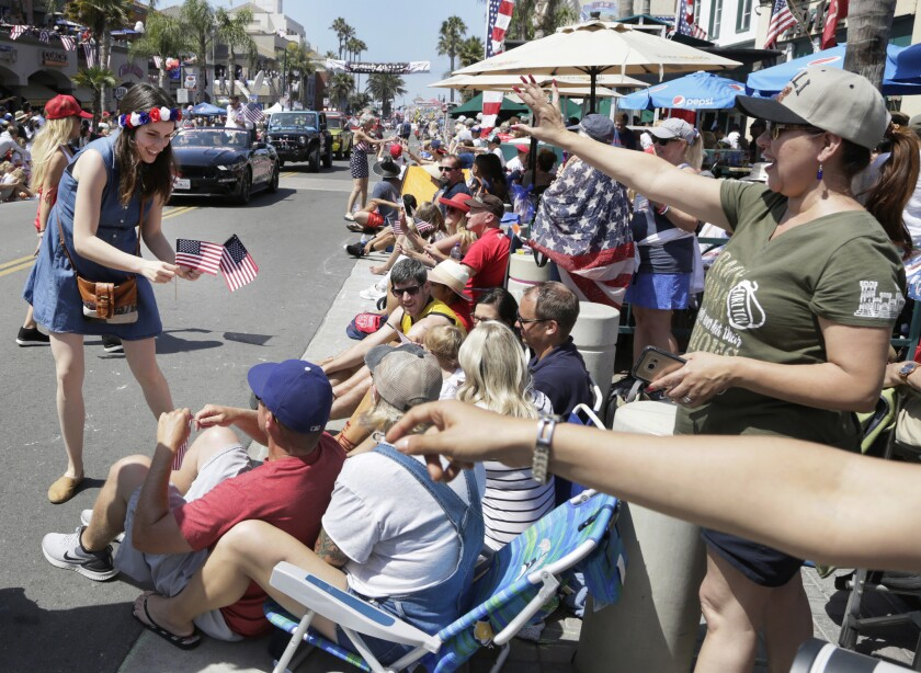 Brana Vlasic hands out American flags for Surf City's Fourth of July Parade in 2019.