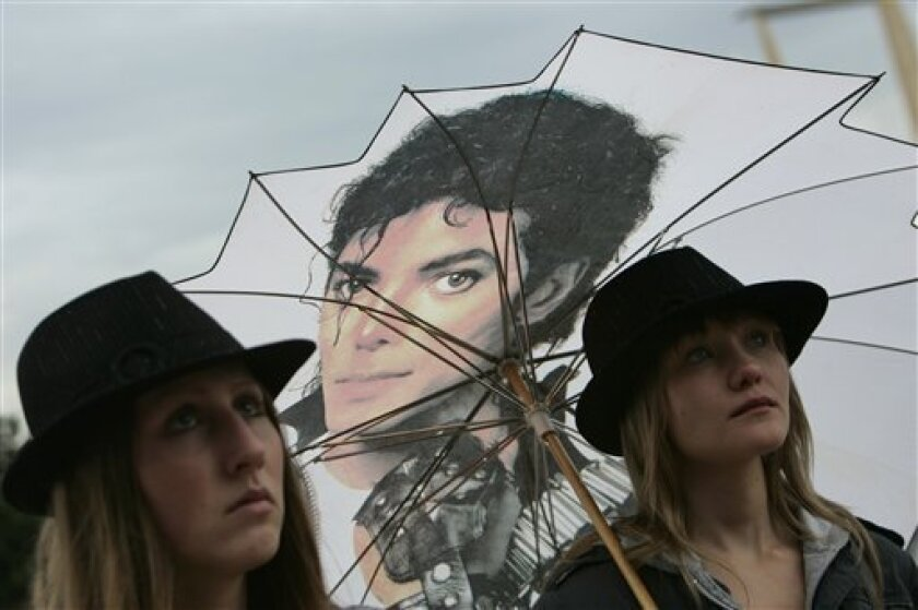 Michael Jackson fans watch his memorial broadcast live from Los Angeles on a TV screen outside the O2 arena in southeast London, Tuesday, July 7, 2009, where he was scheduled to play 50 shows from July 2009. (AP Photo/Lefteris Pitarakis)