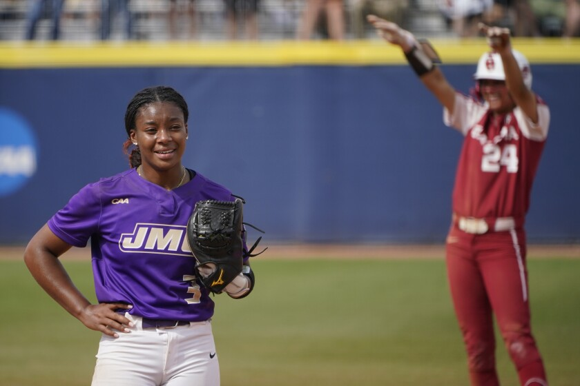 James Madison starting pitcher Odicci Alexander (3) stands in the pitching circle as Oklahoma's Jayda Coleman (24) celebrates at second base behind her after hitting a double in the fifth inning of an NCAA Women's College World Series softball game Monday, June 7, 2021, in Oklahoma City. (AP Photo/Sue Ogrocki)