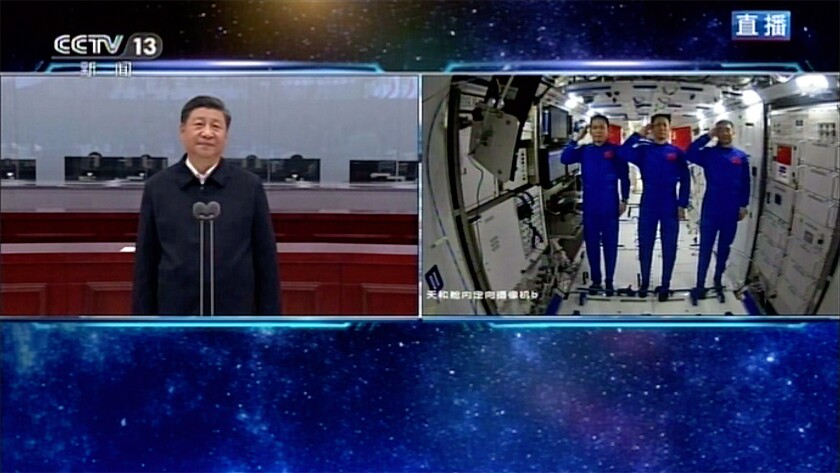 In this image taken from video footage run by China's CCTV, Chinese astronauts, right, salute as they talk with Chinese President Xi Jinping, at the China's new space station in space on Wednesday, June 23, 2021. (CCTV via AP Video)