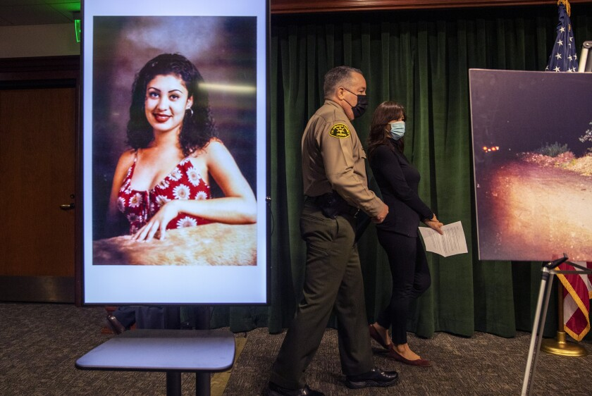 Los Angeles Sheriff Alex Villanueva and Elizabeth Arellano walk past an image of homicide victim Gladys Arellano.