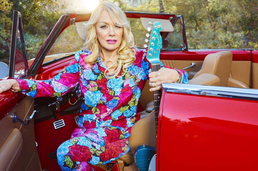 Nancy Wilson sits in a car with her guitar.