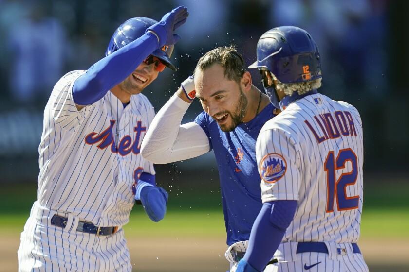 Michael Conforto (centro) de los Mets de Nueva York celebra la victoria 3-2 ante los Marlins