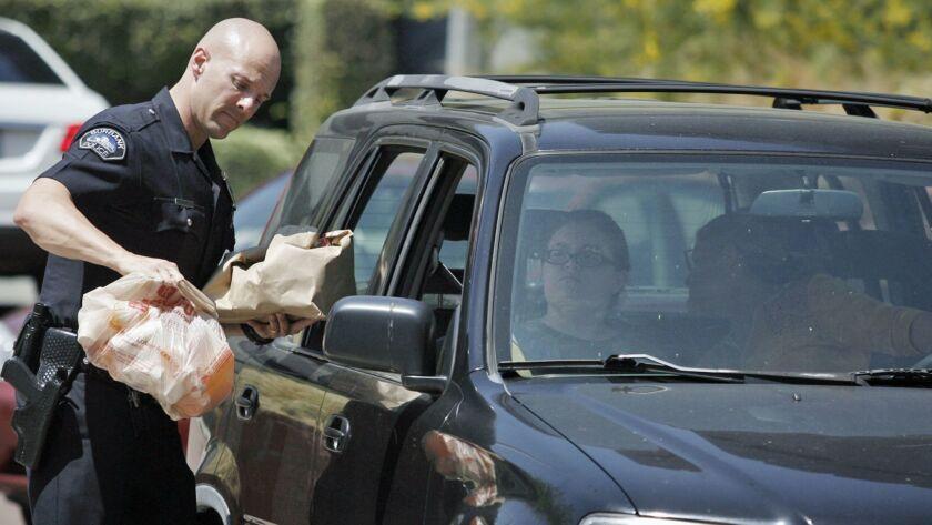 Burbank police officer Joshua Kendrick takes prescription drugs from residents during a drug take–ba