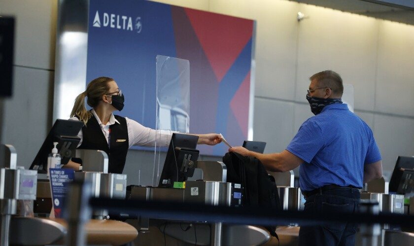 FILE - In this July 22, 2020 photo, a ticketing agent for Delta Airlines hands a boarding pass to a passenger as he checks in for a flight in the main terminal of Denver International Airport in Denver. .Air travel has collapsed because of the virus pandemic, and airlines are trying to convince passengers and their own employees about safety. All airlines require passengers to wear masks during flights, and most extend the rule to airports too. But some people have complained about violators refusing to keep their mask on .(AP Photo/David Zalubowski)