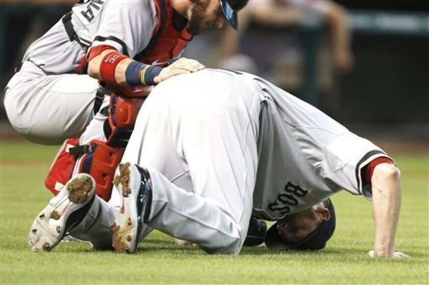 Boston Red Sox catcher Jarrod Saltalamacchia, left, checks on starting pitcher John Lackey after he went down fielding a ball from Houston Astros' Matt Dominguez for the out to end the second inning of a baseball game, Monday, Aug. 5, 2013, in Houston. Lackey was helped from the field. (AP Photo/Pat Sullivan)